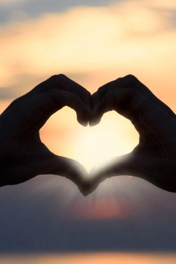 imagem de duas mãos a formar um coração com o por do sol ao fundo