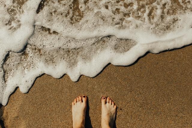 imagem de pés na areia com a água do mar quase a alcançá-los