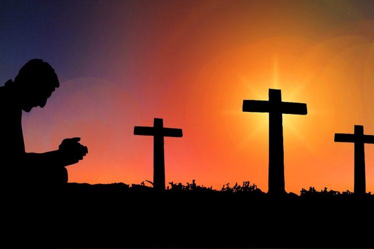 imagem de homem ao por do sol com 3 cruzes