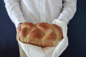 imagem de senhor a segurar um pão envolto num pano branco