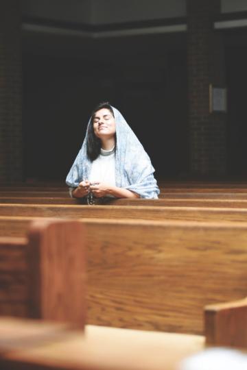 imagem de senhora a rezar em igreja