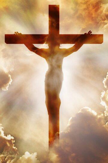 imagem de Jesus na cruz com sol e nuvens por trás