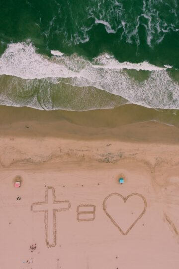 fotografia de cruz e coração escritos na areia da praia