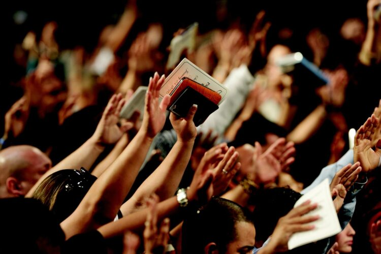 imagem de varias mãos elevadas em clamor, em que uma pessoa está com uma Bíblia nas mãos