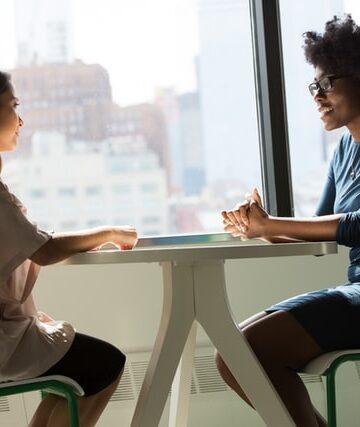 imagem de duas senhoras sentadas frente a frente numa mesa a conversar