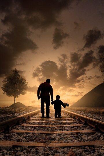 imagem de pai e filho de costas na linha do comboio