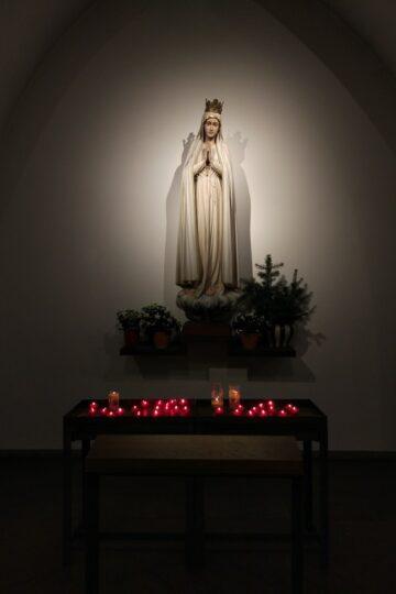 imagem de Nossa Senhora com velinhas acesas aos Seus pés