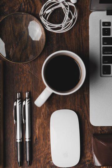 fotografia de mesa de trabalho com um computador, caderno, canetas, caneca de café, fones e uma lupa