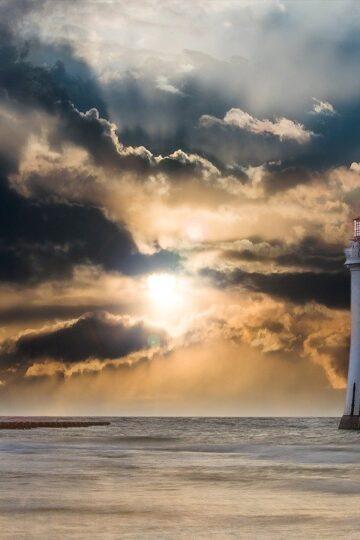 fotografia de farol com sol a descobrir entre as nuvens
