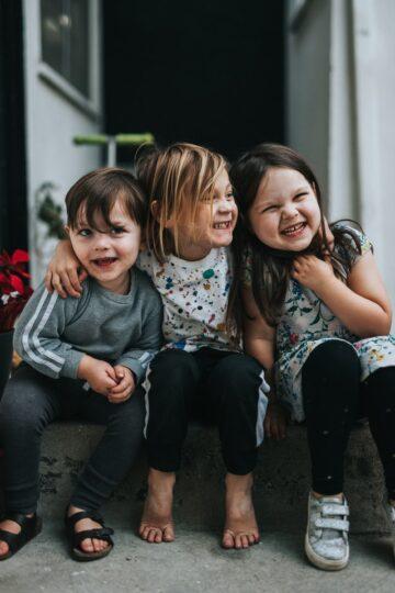 fotografia de 3 crianças sentadas e abraçadas