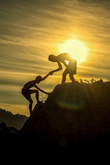 imagem de rapaz a ajudar outro a subir um monte