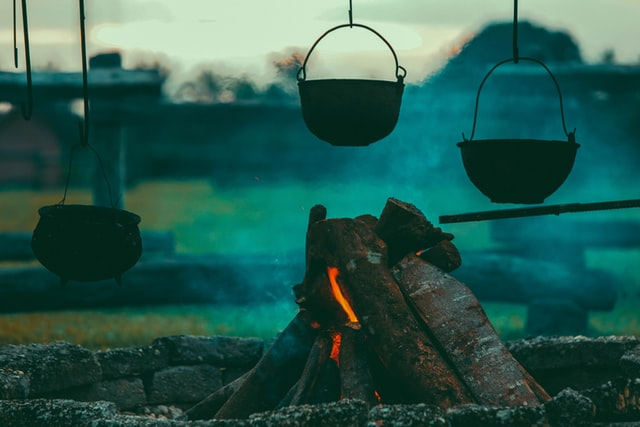 imagem de lenha para fazer lume de chão com panelas penduradas