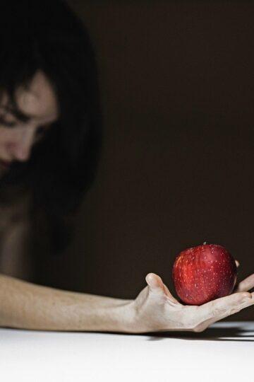 imagem de senhora de mão aberta com uma maçã vermelha na mão