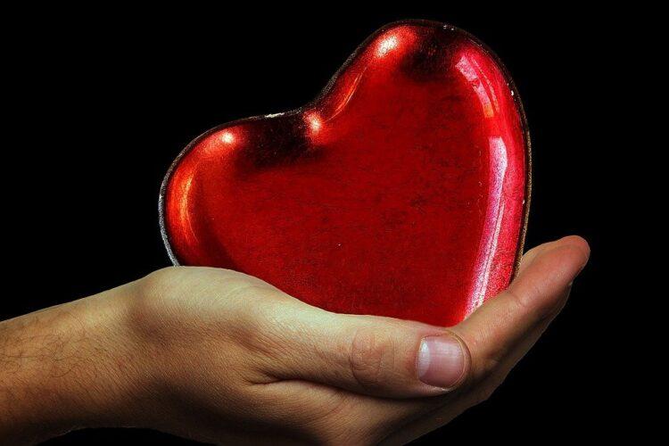 imagem de mão a pegar num coração vermelho