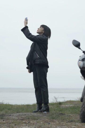 fotografia de senhora a tirar foto ao céu com uma mota ao lado