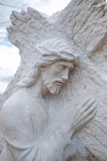 fotografia de escultura de Jesus a carregar a cruz