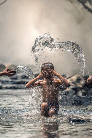 imagem de três crianças a brincar na água