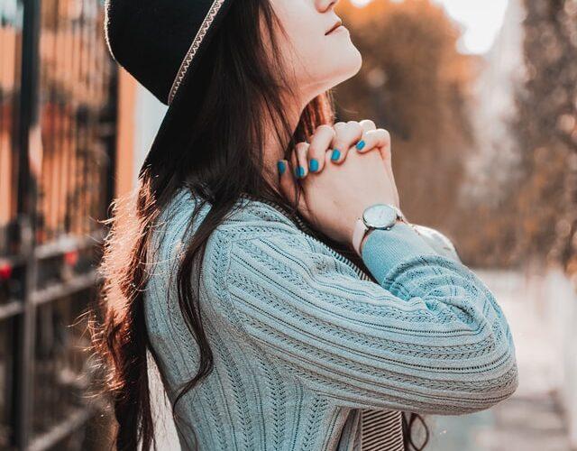 imgem de senhora na rua com as mãos em gesto de oração