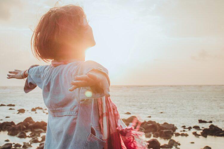 imagem de rapariga de braços abertos ao por do sol