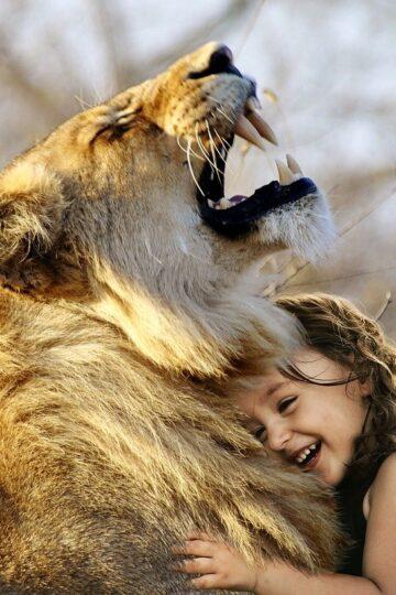 imagem de criança a abraçar um leão